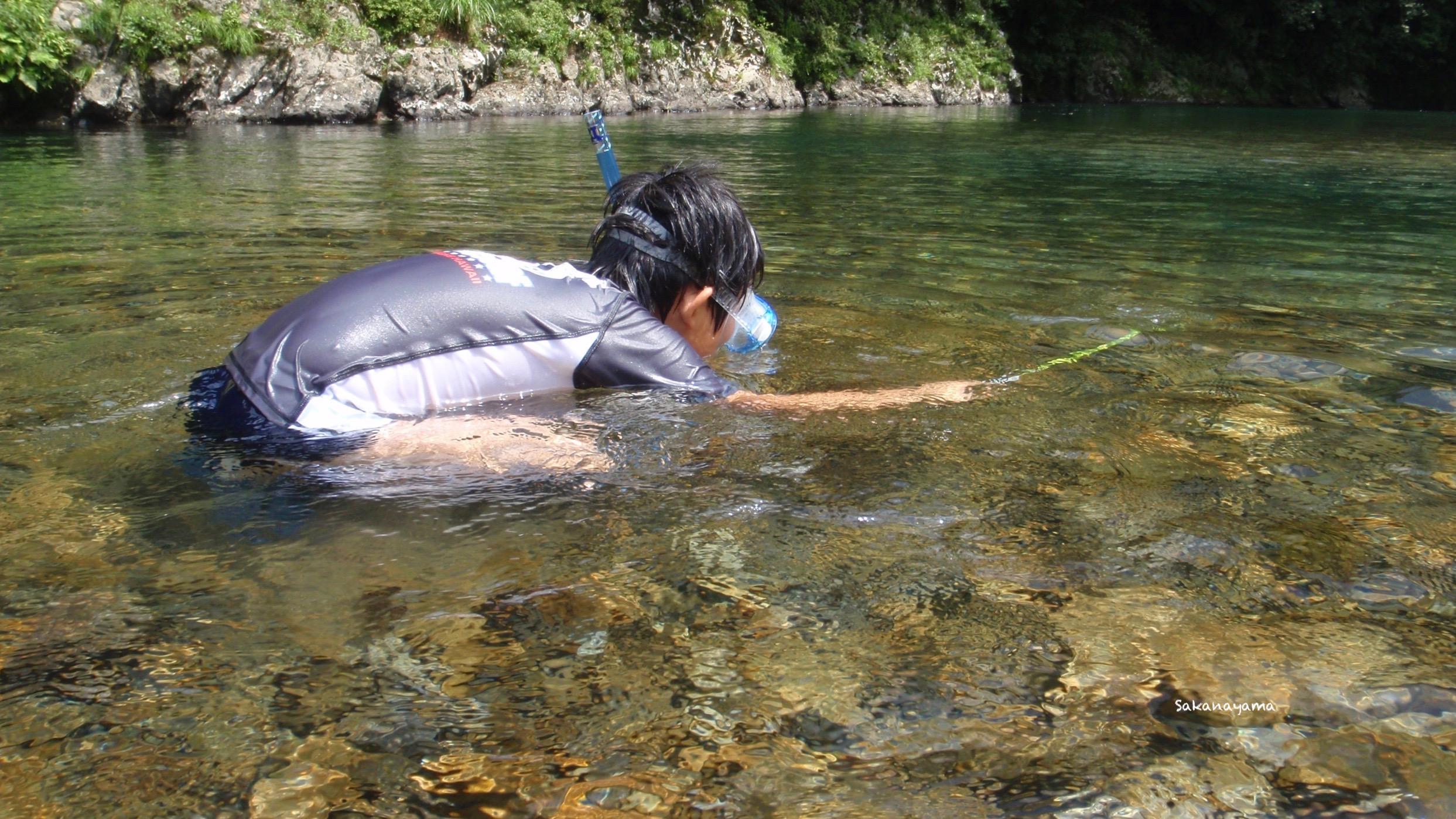 エビタマを持って川で遊ぶ少年